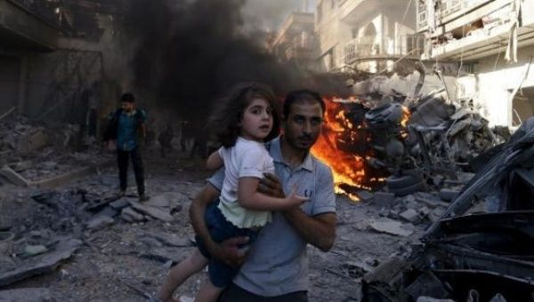 A man carries a young girl after a government airstrike on Douma, a suburb of Damascus.