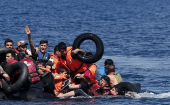 Syrian and Afghan refugees fall into the sea after their dinghy deflated some 100m away before reaching the Greek island of Lesbos, Sept. 13, 2015.