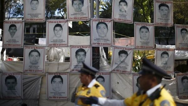 Police stand in front of pictures of the 43 missing Ayotzinapa students as their relatives take part in a meeting with Attorney General Arely Gomez, Jan. 14, 2016.