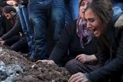 Relatives of Siyar Salman mourn over his grave during a funeral ceremony in the Kurdish dominated southeastern city of Diyarbakir, Turkey.