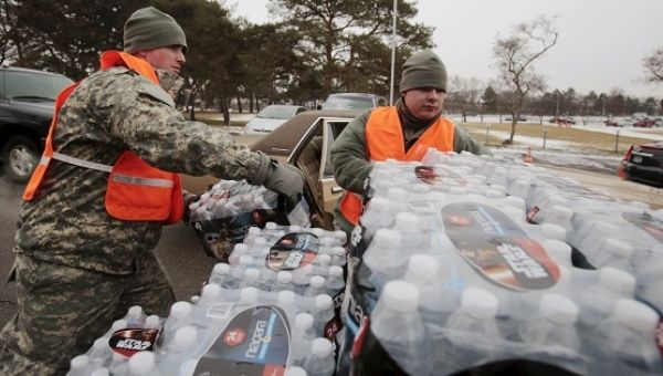 Michigan National Guard members help to distribute water to a line of residents in their cars in Flint, Michigan.