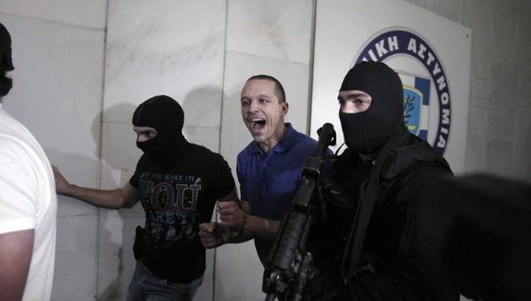 Golden Dawn spokesman and lawmaker Ilias Kasidiaris (C) shouts as he is escorted by police officers to police headquarters in Athens, Greece, Sept. 28, 2013.