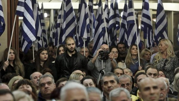 Supporters at a Golden Dawn meeting listen to a speech by lawmaker Ilias Panagiotaros during election campaigns in Athens, Greece, Jan. 21, 2015.