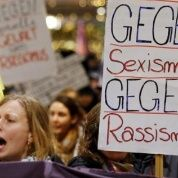 "Women shout slogans and hold up a placard that reads ""Against sexism, Against Racism"""