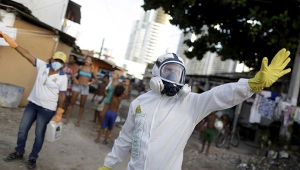 Municipal workers gesture before spraying insecticide at the neighborhood of Imbiribeira in Recife.