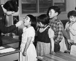 Nurse Desrochers checks a girl's throat while other children wait in line, at the Frobish Bay Federal Hostel in Iqaluit, Nunavut, in a 1959 archive photo.