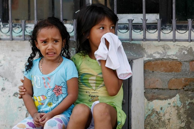 Two girls wait outside their house while members of the Cali Health Ministry fumigate the area, Jan. 28, 2016.