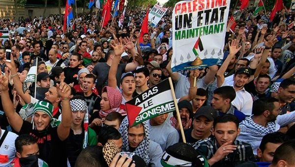 "Palestine protesters hold up banners that read ""Palestine is a State."""