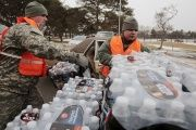 Michigan National Guard members help to distribute water to a line of residents in their cars in Flint, Michigan, on Jan. 21, 2016.