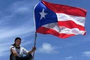 A Puerto Rican man holds up his nation's flag during a May Day event in Vieques, Puerto Rico, May 1, 2003.