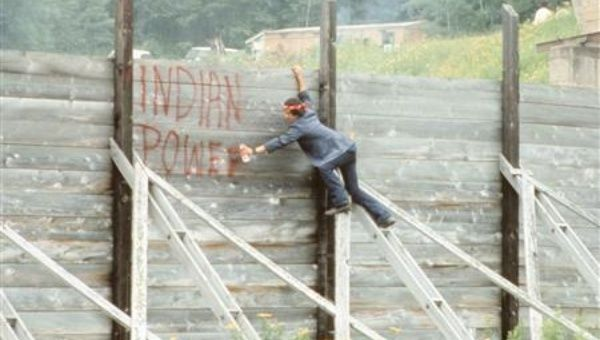 Rick St. Germaine sprays a message on the wall of the Winder Dam