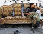 A Free Syrian Army fighter relaxes on a sofa in the old city of Aleppo, Syria.
