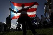 A protester holding a Puerto Rico's flag takes part in a march in San Juan