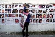 A woman holds onto a banner with the photographs of missing women in Ciudad Juarez Jan. 28, 2015.