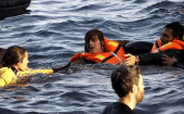 A volunteer lifeguard (L) helps a refugee as a half-sunken catamaran carrying around 150 refugees, most of them Syrians, arrives after crossing part of the Aegean sea from Turkey on the Greek island of Lesbos, Oct. 30, 2015.