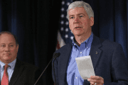 Michigan Governor Rick Snyder holds a rebate check for US$1.2 million dollars to hand to Detroit Mayor Mike Duggan, Detroit, on Dec. 10, 2014.