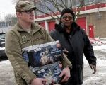 Michigan National Guard Staff Sergeant William Phillips (L) assists a Flint resident with bottled water at a fire station in Flint, Michigan Jan. 13, 2016.