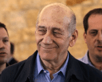 Ehud Olmert leaves Israel's Supreme Court in December 2015 after the court upheld one bribery conviction but acquitted him of another.