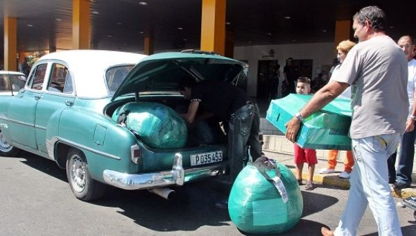 A visitor from the U.S. loads his luggage into one of Cuba