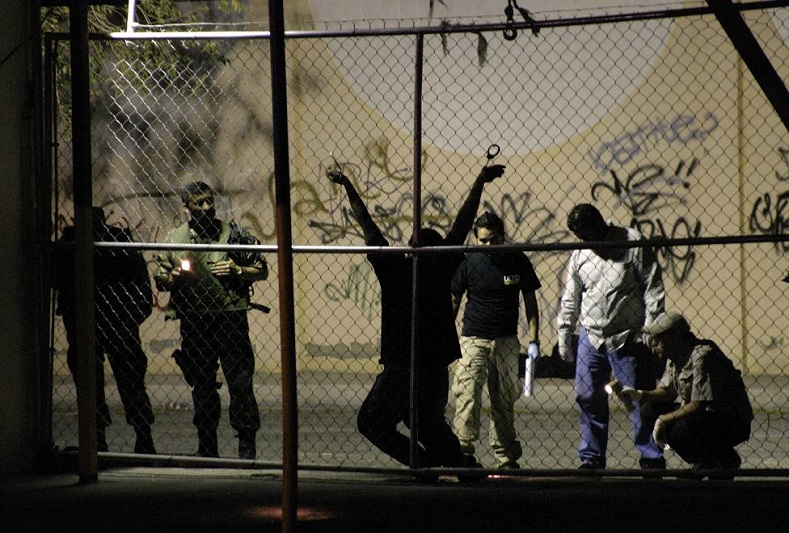 Military and forensic experts inspect the body of a man who was killed outside a nightclub in the border city of Ciudad Juarez August 31, 2009. A man was handcuffed to a fence and shot several times by drug hit men outside a nightclub, according to local media.