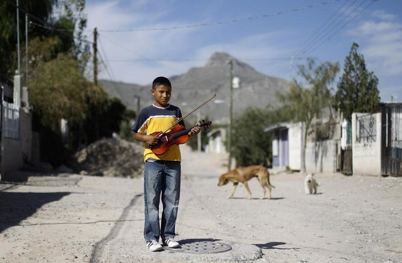 Ten year old jose angel holds his violin while posing for a photograph