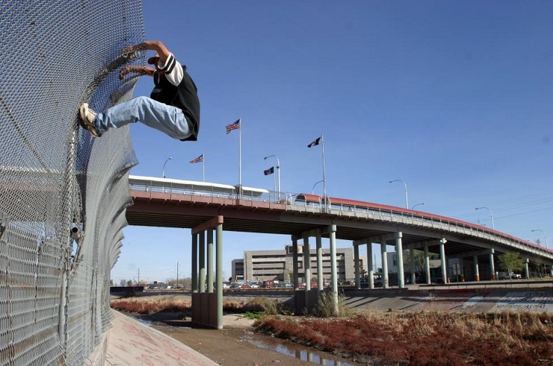 A migrant tries to cross into the U.S. from the Mexican border town of Ciudad Juarez, under the bridge that connects the border city with El Paso March 6, 2006.