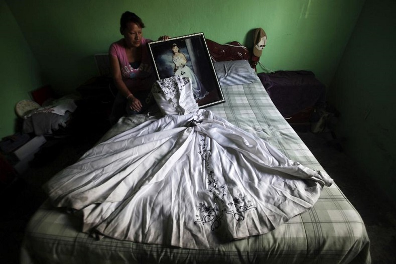 Luz Elena Munoz holds a photograph of her daughter Nancy Ivette Navarro Munoz while sitting next to the dress of Nancy