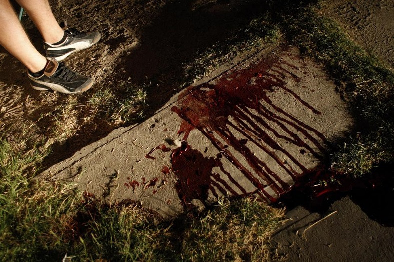 A resident stands next to bloodstains of a man who was gunned down by unknown assailants in the border city of Ciudad Juarez March 3, 2009.