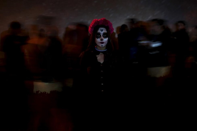 "A woman with her face painted as the popular Mexican figure ""Catrina"" poses for a photograph during Day of the Dead celebrations in Ciudad Juarez November 2, 2015."