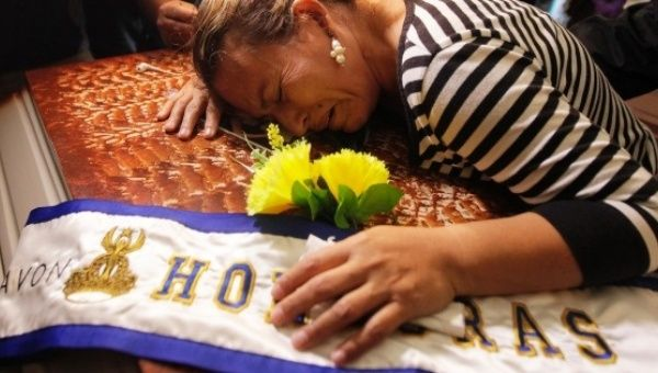 Teresa Munoz mourns over the coffin of her daughter Maria Jose Alvarado during a wake for Maria Jose and her sister Sofia in Honduras, Nov. 20, 2014.