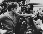 A pro-apartheid supporter attacks black South Africans during a rally in 1989.