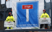 Geenpeace activists display a banner as they block the main entrance of a conference centre where negotiators are expected to discuss the 12th Round of the Transatlantic Trade and Investment Partnership (TTIP) in Brussels, Belgium, Feb. 22, 2016.