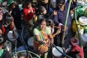 Residents fill their empty containers with water from a municipal tanker in New Delhi, India.