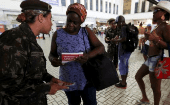 A Brazilian Army soldier distributes pamphlets with information to combat the Aedes aegypti mosquito during the National Day of Mobilization Zika Zero at Central train station in Rio de Janeiro, Brazil, Feb. 13, 2016.
