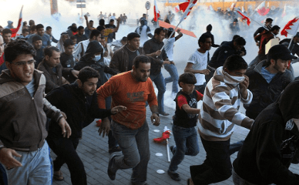 Bahraini protesters run for cover from tear gas fired by police to disperse them in the village of Sanabis near Manama on Feb. 14, 2011 during a demonstration called for on Facebook.
