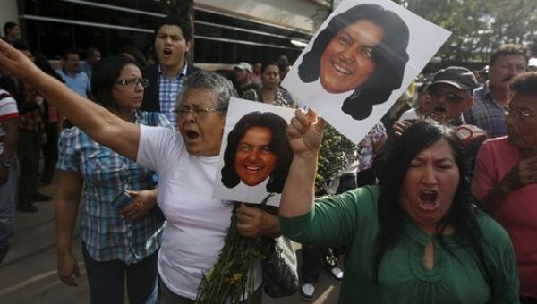 Activists hold photos of slain environmental rights activist Berta Caceres and shout after her body was released from the morgue in Tegucigalpa, March 3, 2016.