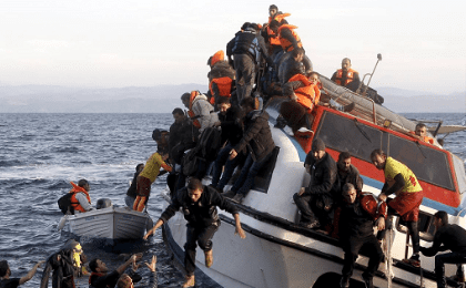 Refugees, most of them Syrians, on a half-sunken catamaran nearing the Greek island of Lesbos.