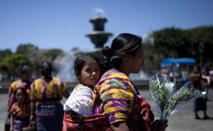 An Indigenous woman walks with her daughter after participating in the commemoration of International Women