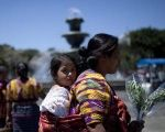 An Indigenous woman walks with her daughter after participating in the commemoration of International Women's Day today in the Central Park Guatemala city.
