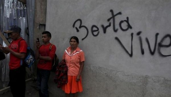 "Supporters of slain Indigenous activist Berta Cáceres wait beside a wall, which reads ""Berta Lives,"" during her funeral in La Esperanza, Honduras March 5, 2016."
