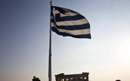 A Greek flag flutters in the wind above the Acropolis in Athens.