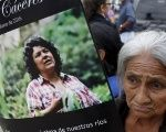 A woman holds up a poster with an image of Berta Caceres along a street during her funeral in the town of La Esperanza, Honduras, March 5, 2016.