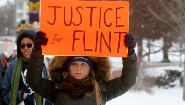 Demonstrators protest over the Flint, Michigan, contaminated water crisis outside of the venue where the Democratic U.S. presidential candidates