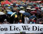 Taiwanese holding placards take part in the annual anti-nuclear protest during a downpour in Taipei, Taiwan.