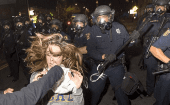 A protester flees as police officers try to disperse a crowd comprised largely of student demonstrators during a protest against police violence in the U.S., in Berkeley, California early Dec. 7, 2014.