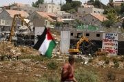 A Palestinian flag as Israeli heavy machinery demolish apartment blocs in the West Bank Jewish settlement of Beit El July 29, 2015.