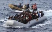 Migrants sit in a boat during a rescue operation by Italian navy off the coast of the south of the Italian island of Sicily in this November 28, 2013 picture provided by the Italian Marina Militare.
