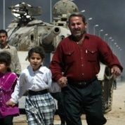 A family flees past a destroyed Iraqi T-55 tank after a mortar attack on British Army positions in the southern city of Basra, March 28, 2003.