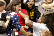 A member of the audience (R) throws a punch at a protester as Republican Presidential candidate Donald Trump speaks during a campaign event in Tucson, Arizona March 19, 2016.