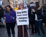 A woman holds a sign protesting the NYPD programme during a rally at Foley Square in New York.